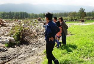 流木や岩が流れ込んだ牧草地の惨状を前に言葉を失う蓮舫代表
